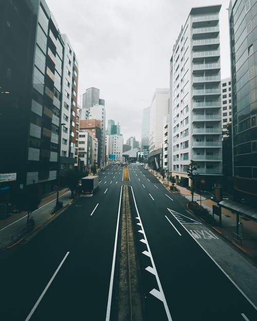 Cars on Road Between High Rise Buildings
