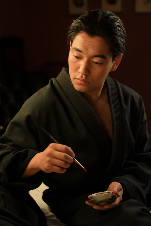 Man in Black Robe Holding a Paintbrush