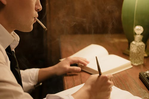 Man Smoking and Writing on His Notebook