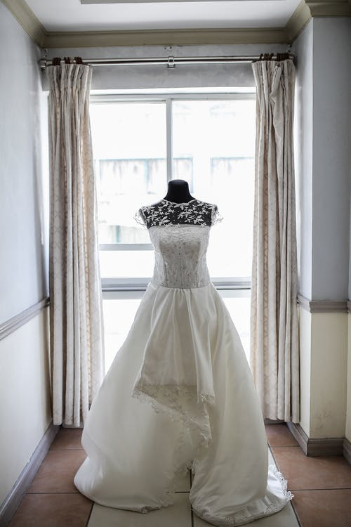 White Floral Wedding Gown on White Window Curtain