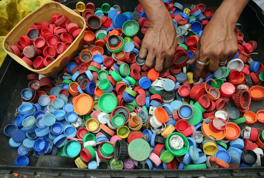 Person Hands on Assorted-color Plastic Lid Lot
