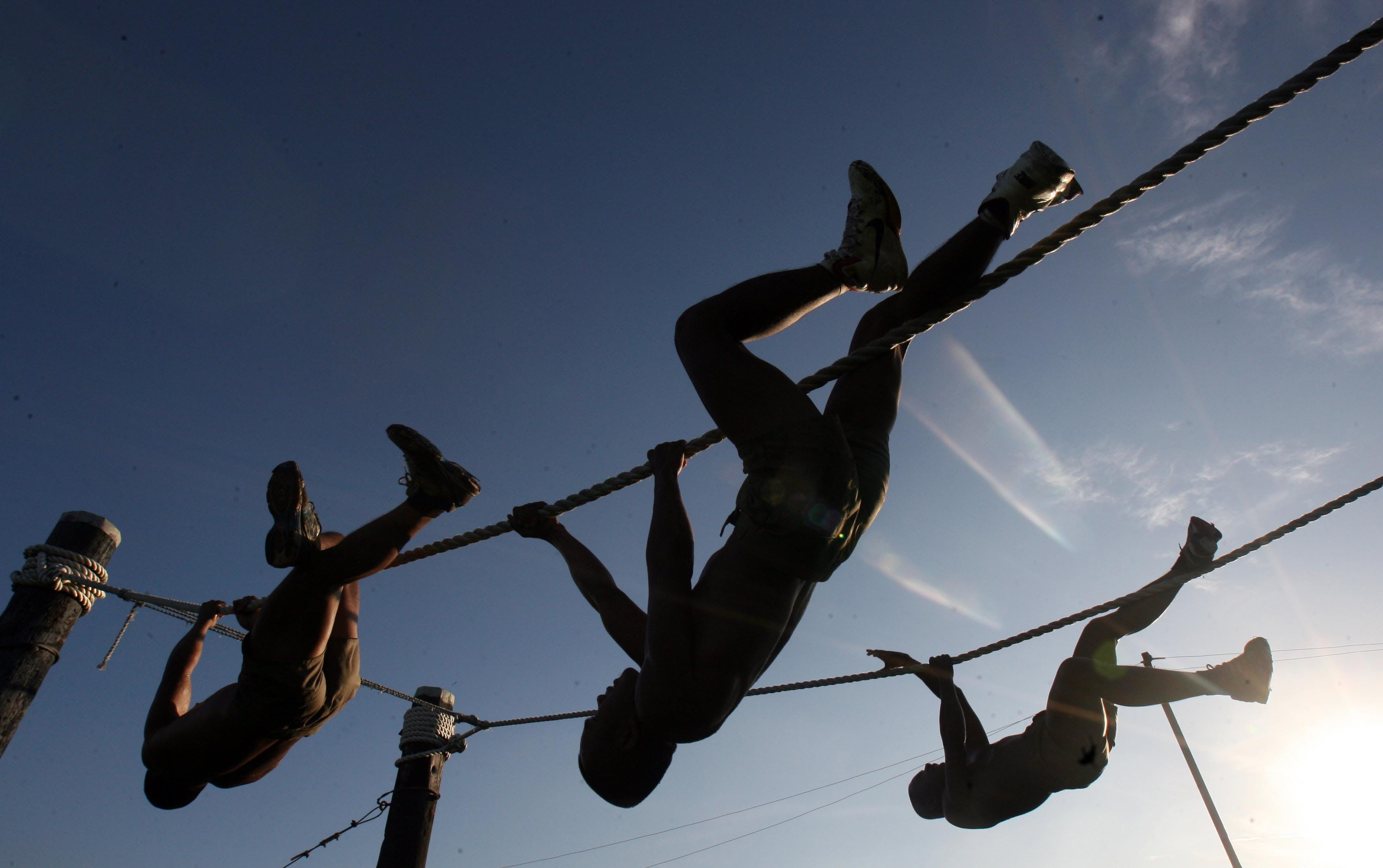 Three Man Climbing on Rope Under the Sunset