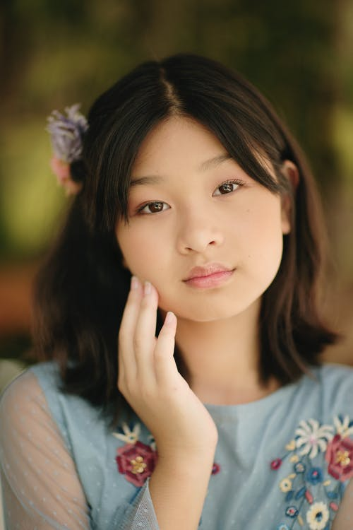 Charming Asian female looking at camera against blurred background