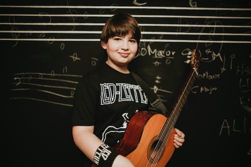 Cheerful teenage boy with guitar near chalkboard