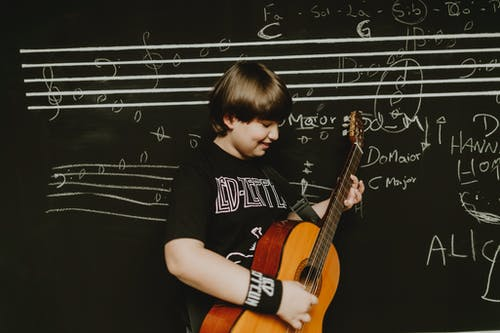 Side view of teenage boy in t shirt playing song on acoustic guitar while standing near chalkboard with musical notes