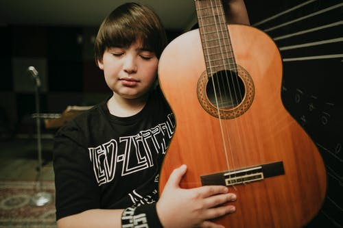 Dreamy boy with acoustic guitar in music school
