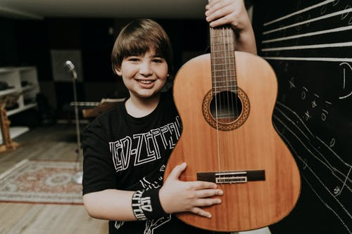 Cheerful boy with classic guitar looking at camera against chalkboard with staves in music school