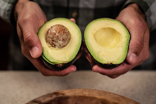 High angle of crop anonymous male demonstrating ripe halved avocado while standing at table