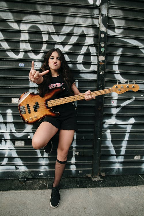 A Girl Holding a Electric Bass Guitar
