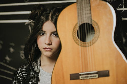 Woman Holding Brown Acoustic Guitar
