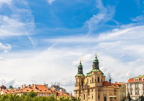 Exterior of aged Saint Nicholas church placed in Prague under cloudy blue sky in sunny day