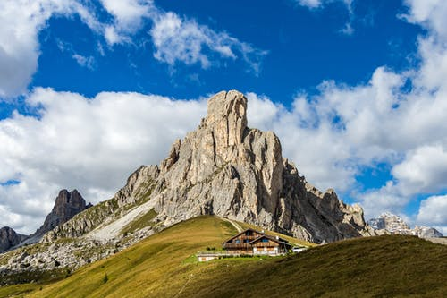 Picturesque scenery of wooden houses placed on grassy hill near rocky Dolomite Mountains against cloudy blue sky in daylight