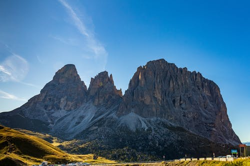 Picturesque landscape of massive rough rocky Dolomite Mountains located in Italy against cloudless blue sky in sunny sunny day