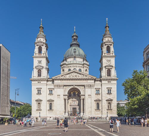 Tourists strolling on square in front of old Catholic St Stephens Basilica in Budapest under blue sky