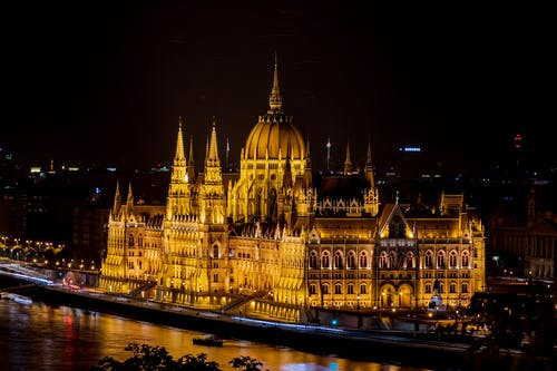 Illuminated Gothic building with glowing lights on river bank