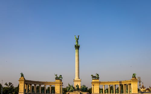Low angle of Heroes Square and column with Archangel Gabriel on top against colonnades in Budapest