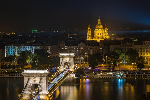 Medieval suspension Szechenyi Chain Bridge connecting shores of Danube river in Budapest at dark night