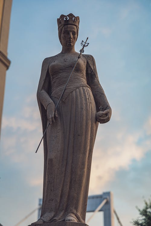 From below of aged stone sculpture of saint duchess in crown with mace and scepter in Budapest