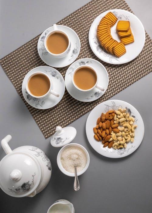 White Ceramic Teacup With Saucer and Sliced Orange Fruit on White Ceramic Saucer