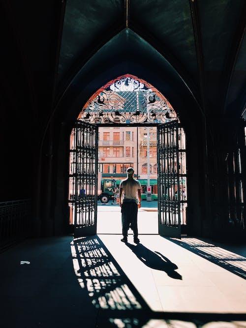 Woman in Gray Long Sleeve Shirt Standing Near Black Metal Gate