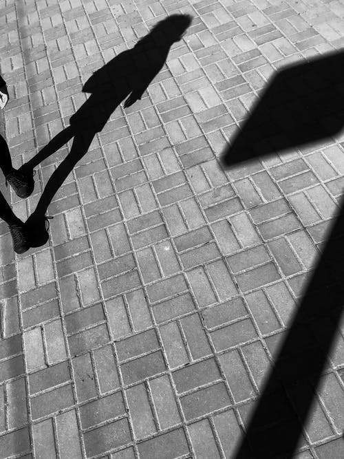 Shadow of person walking on street in sunny day