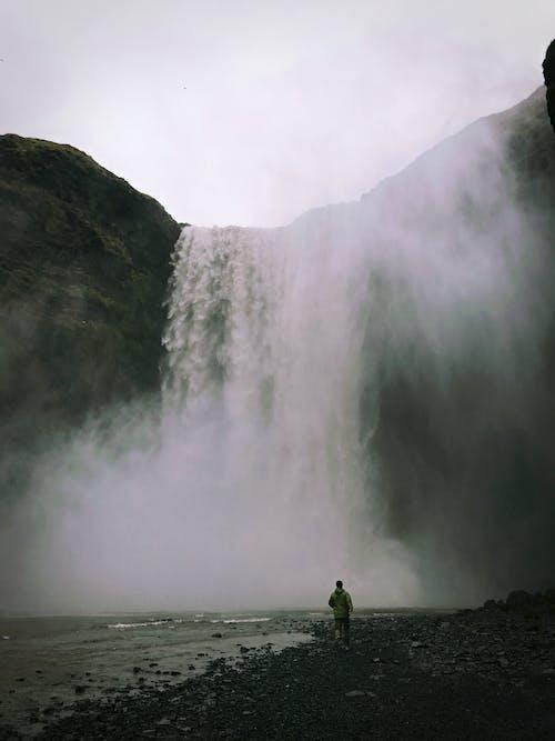 Person in Green Jacket Standing Near Waterfalls