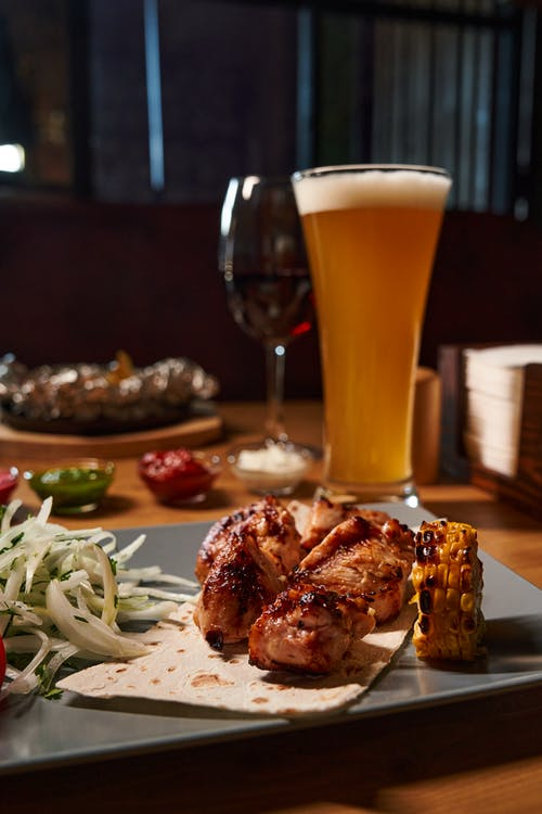 Cooked Meat on Plate Beside Clear Drinking Glass With Beer