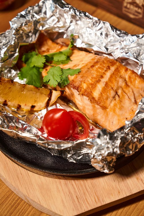 From above of appetizing foil roasted fish fillet with lemon tomatoes and herbs placed on iron skillet pan on wooden table