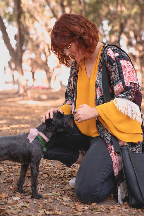 Woman Smiling while Looking at Her Dog