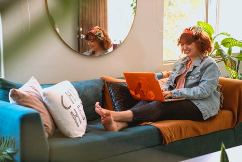 Woman Sitting on Sofa while Using Her Laptop