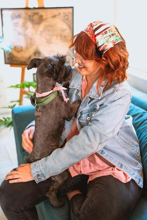 Woman in Light Blue Denim Jacket Smiling while Holding Her Dog