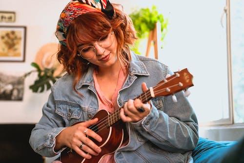 Woman in Blue Denim Jacket Playing Brown Acoustic Guitar