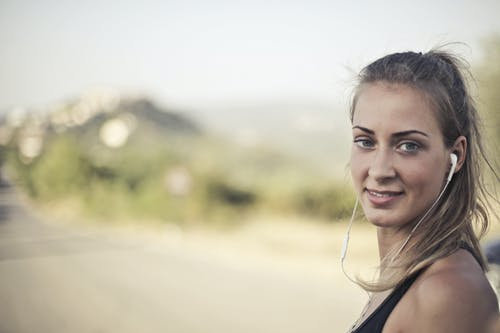 Woman Wearing Black Tank Top And White Earbuds