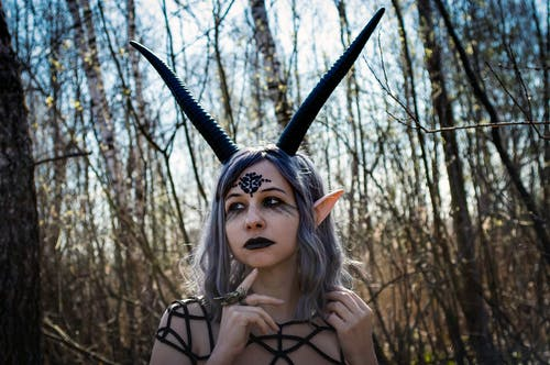 Portrait of young woman with black makeup and purple hair and black horns looking away in forest