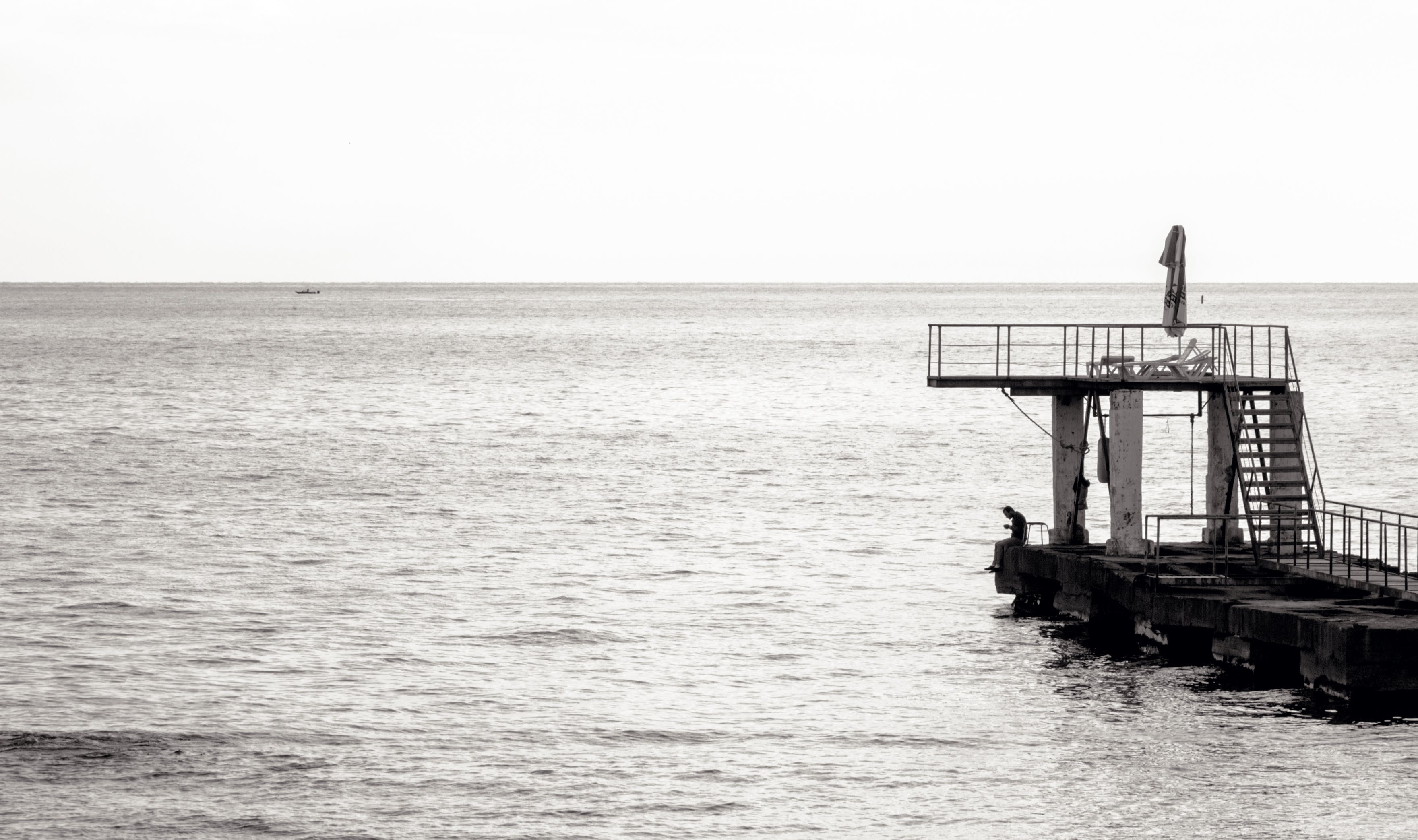 Grayscale Photo of Sea Diving Port