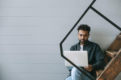 Man in Black Jacket Sitting on Chair Using Silver Macbook