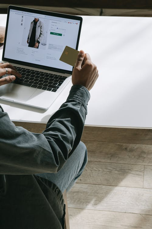 Person in Blue Denim Jeans Using Macbook Pro