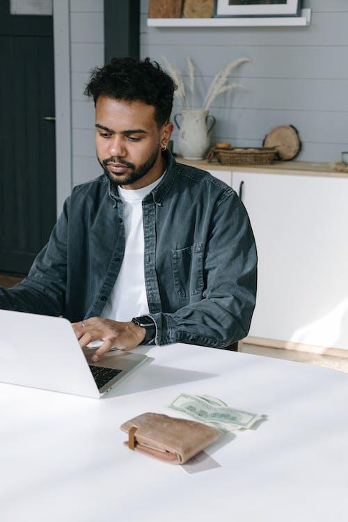Man in Black Jacket Using Macbook