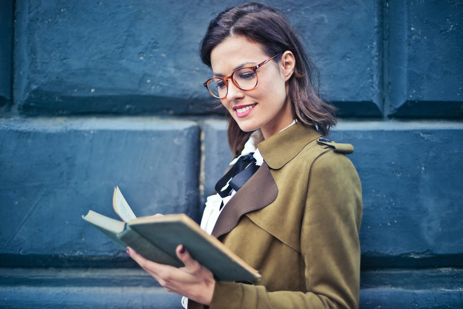 Woman In Brown Suede Peacoat Reading A Book