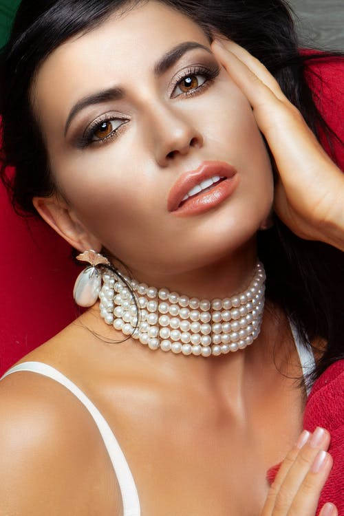 Gorgeous woman with necklace and earrings looking at camera
