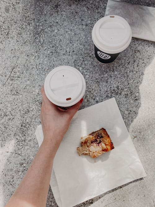 Unrecognizable woman drinking coffee to go and eating dessert on street