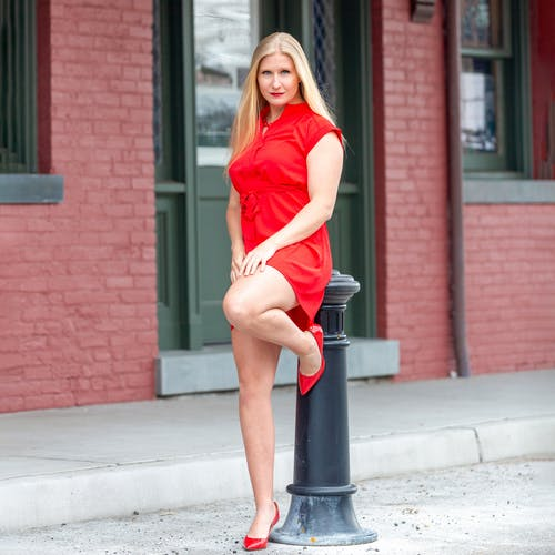 Woman in Red Dress Sitting on Red Metal Post