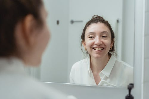 Woman in White Dress Shirt Smiling In Front of a Mirror