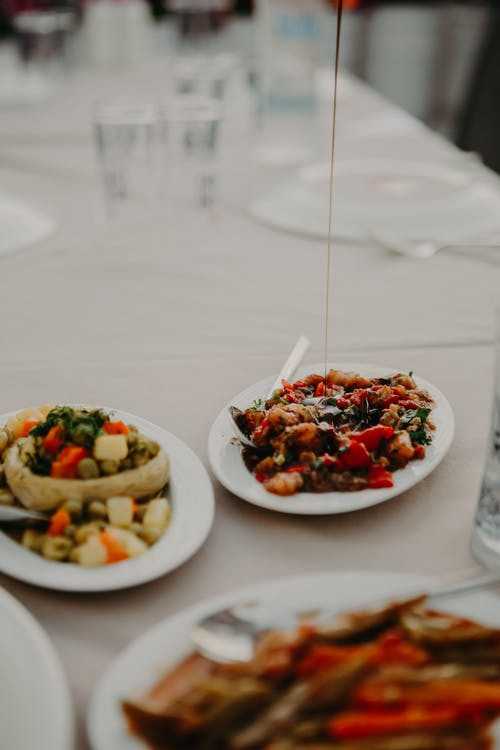 Delicious appetizing dishes served on white plates on table with glassware at banquet in restaurant