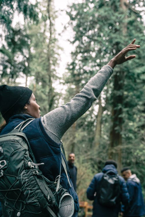 Woman Carrying a Backpack while Pointing Upwards