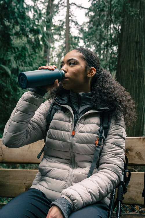 Woman in White Bubble Jacket Drinking from a Tumbler
