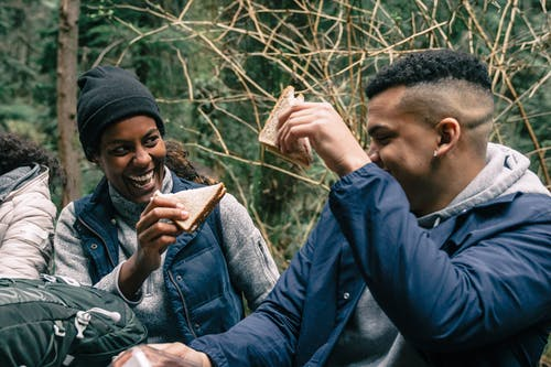 Man and Woman Having Fun while Eating Sandwiches