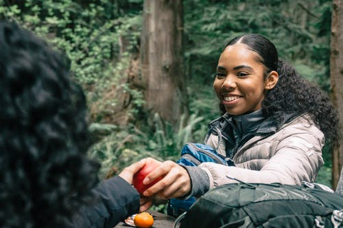 Woman Smiling while Sharing an Apple