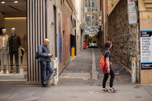 Man in Red Jacket Walking on Sidewalk