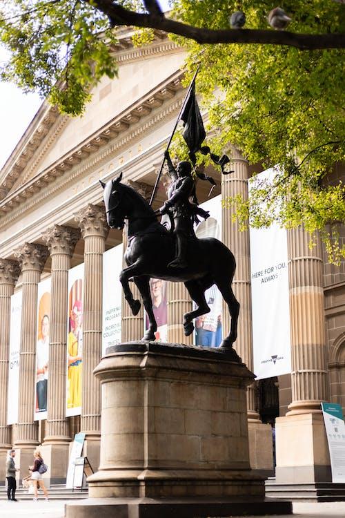 Black Horse Statue Near White Concrete Building